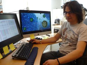 Dr. Alexander Suh at work in front of his PC. The screen depicts hepatitis B viruses