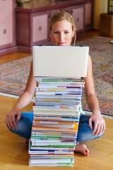 Eine Studentin sitzt vor einem Stapel Bücher und einem Laptop Computer