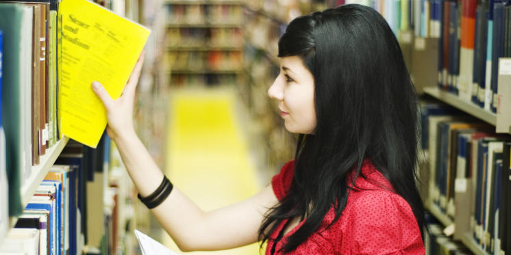 Young woman takes book from shelf