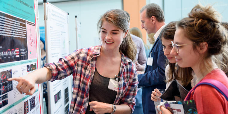 Photo of a discussion situation between young researchers during a poster presentation at a scientific symposium