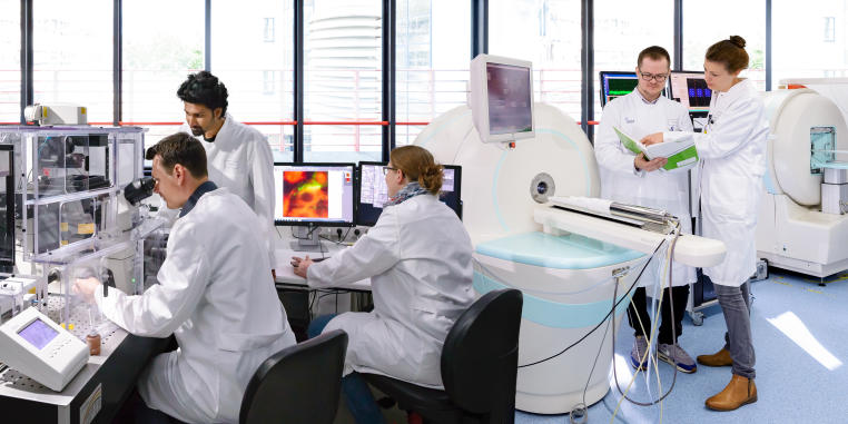 Picture of people working together with different imaging modalities in a laboratory