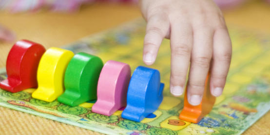 Child's hand with game pieces