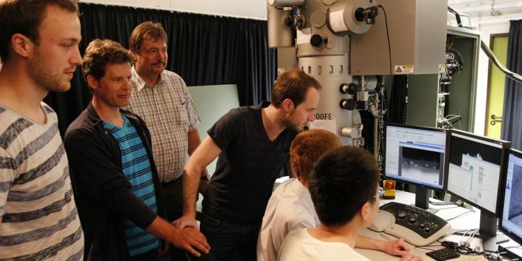 Prof. Dr. Wolfram Pernice (2.v.l.) und Prof. Dr. Gerhard Wilde (3.v.l.) mit Mitarbeitern an einem Transmissions-Elektronenmikroskop am Institut für Materialphysik