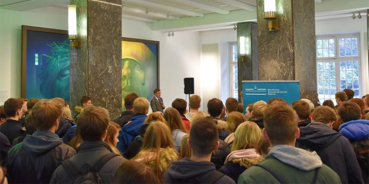 Im Foyer des Schlosses lauschen die Erstsemester der Wirtschaftswissenschaftler der Rede des Rektors.<address>&copy; WWU - Friederike Stecklum</address>