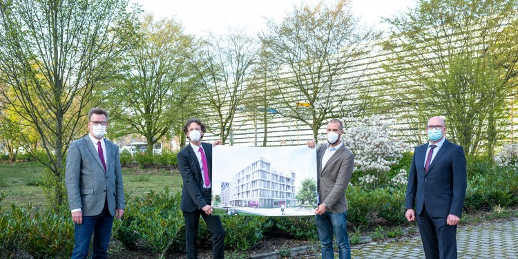Rector Prof. Johannes Wessels (left) and Head of Administration Matthias Schwarte (right) present the plans for the new research building with mathematicians Prof. Mario Ohlberger (2nd from left) and Prof. Thomas Nikolaus. The visualization, produced by the Münster office of North Rhine-Westphalia's Buildings and Real Estate Management Department, gives a first impression of the building which will be constructed near Coesfelder Kreuz.<address>© WWU - Michael Möller</address>